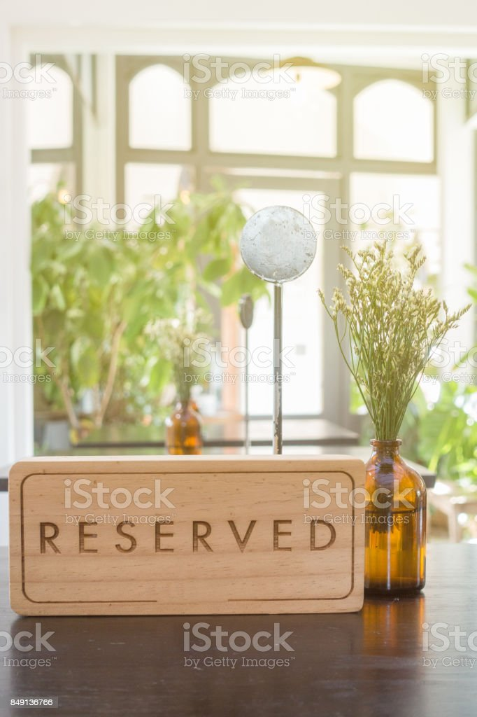 Wooden reserved table sign with empty steel label for table in restaurant with small flower vas. stock photo
