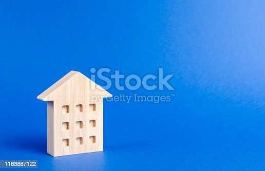 istock A wooden residential building stands on a blue background. The concept of buying and selling real estate, renting. Search for a house. Affordable housing, credit and loans. Investments. place for text 1163887122