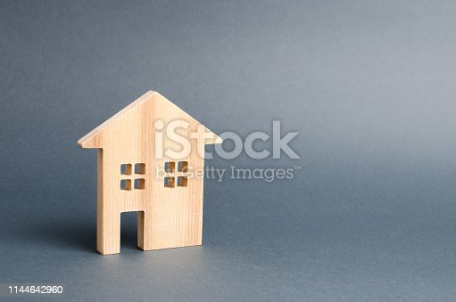istock Wooden residential house on a gray background. Mortgage and credit for the purchase. Minimalism. Isolate Real estate concept, buying affordable housing, real estate renting. Property tax. 1144642960