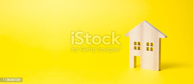 istock Wooden residential house on a yellow background. Mortgage and credit for the purchase. Minimalism. Isolate Real estate concept, buying affordable housing, real estate renting. Property tax. Banner 1136382091