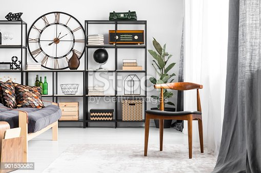 Wooden retro chair and sofa with patterned pillows in living room with industrial shelves and clock