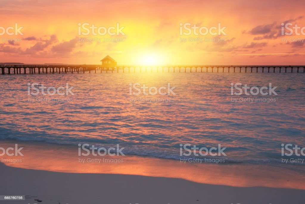 wooden road from the island to a hut over water on a sunset. Maldives. stock photo