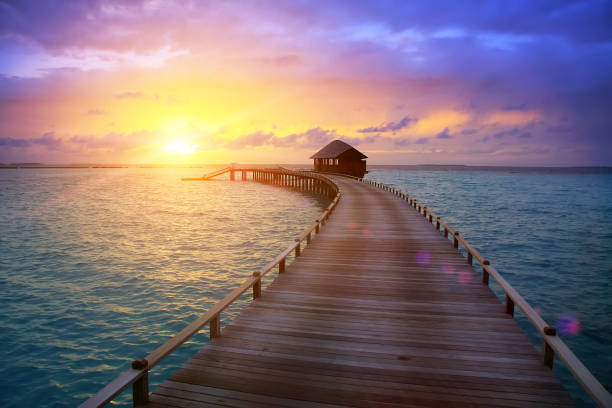 wooden road from the island to a hut over water on a sunset. Maldives.