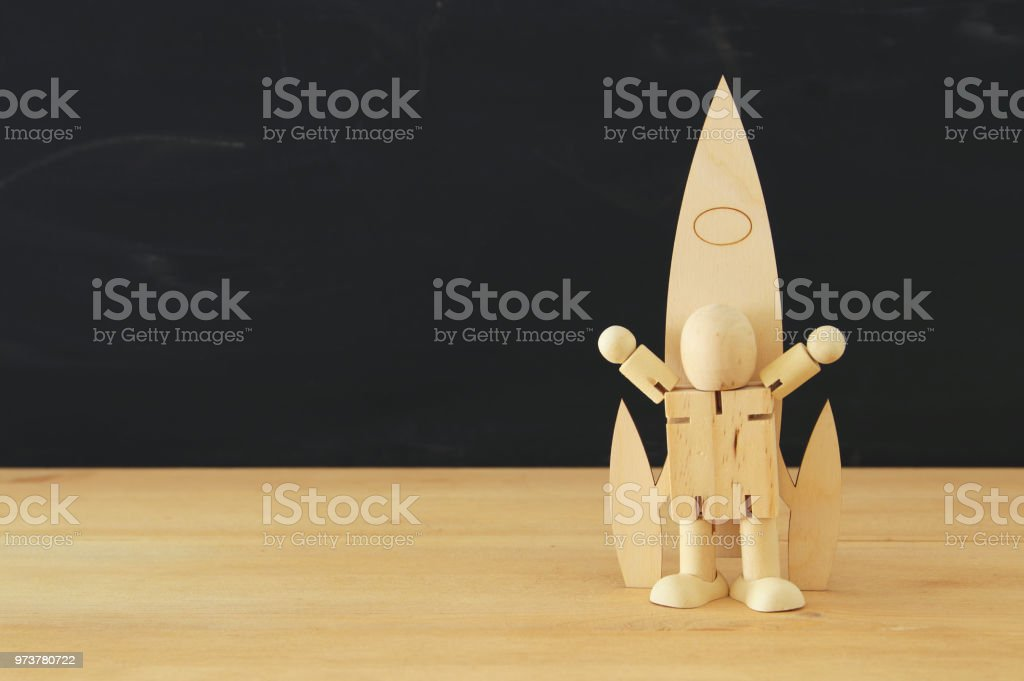 wooden rocket and dummy in front of classroom blackboard. stock photo