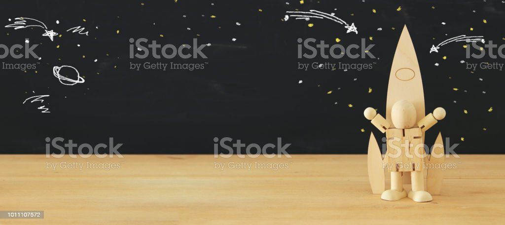 wooden rocket and dummy with space sketches in front of classroom blackboard. stock photo