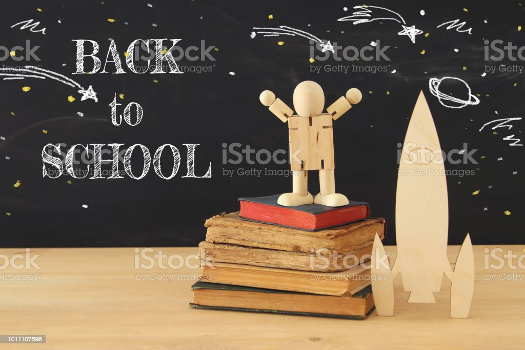 wooden rocket and space sketches with wooden dummy in front of classroom blackboard. stock photo