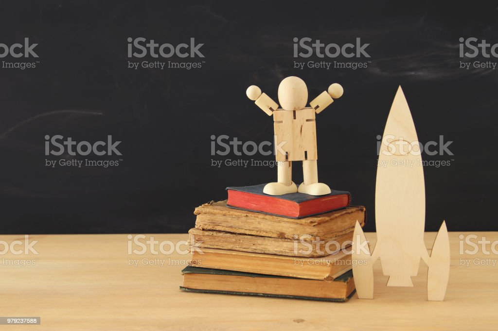 wooden rocket with wooden dummy in front of classroom blackboard. stock photo