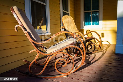 Wooden rocking chair on front porch at sunset nobody