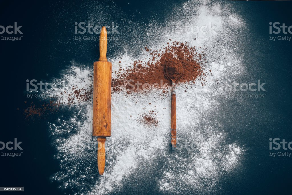 wooden rolling pin with flour and a spoon of cocoa on a black and blue background. Concept: creative chaos stock photo