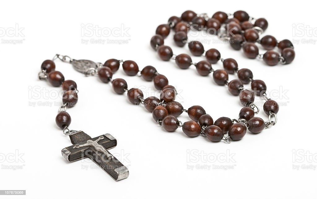 Wooden rosary beans laid across a white table stock photo