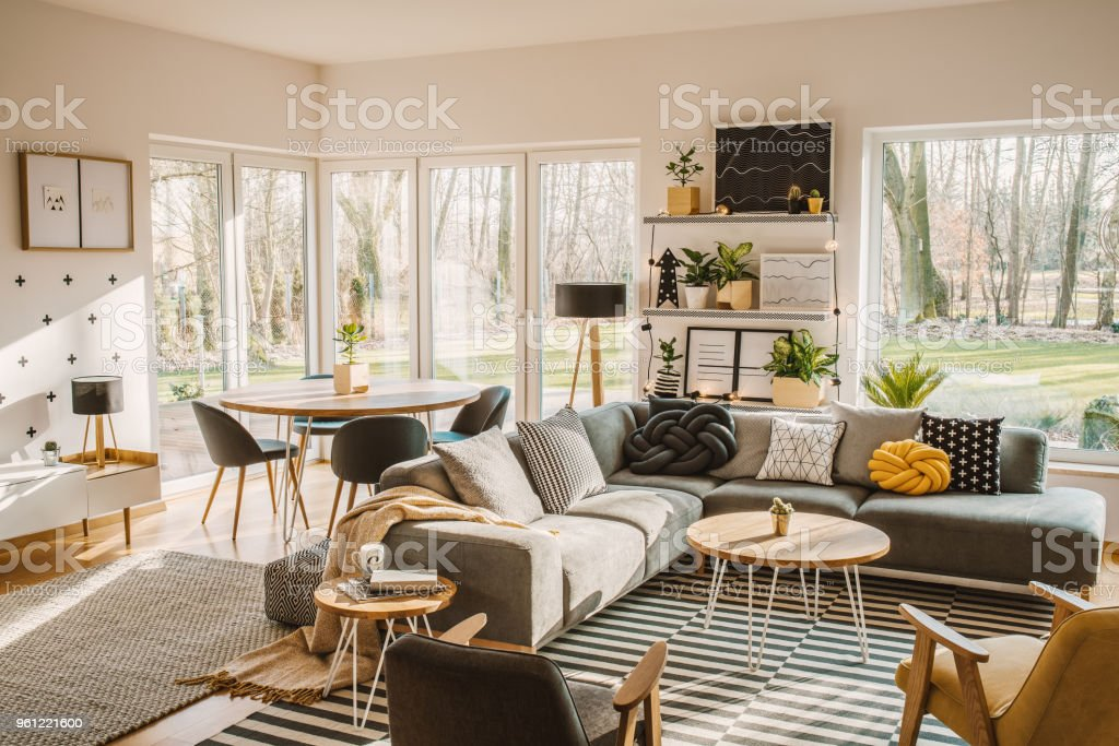 Wooden Round Dining Table In The Corner Of An Open Space Living Room  Interior With Nordic Furniture And Decor Stock Photo - Download Image Now