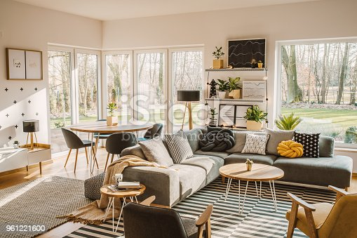 Wooden, round dining table in the corner of an open space living room interior with nordic furniture and decor