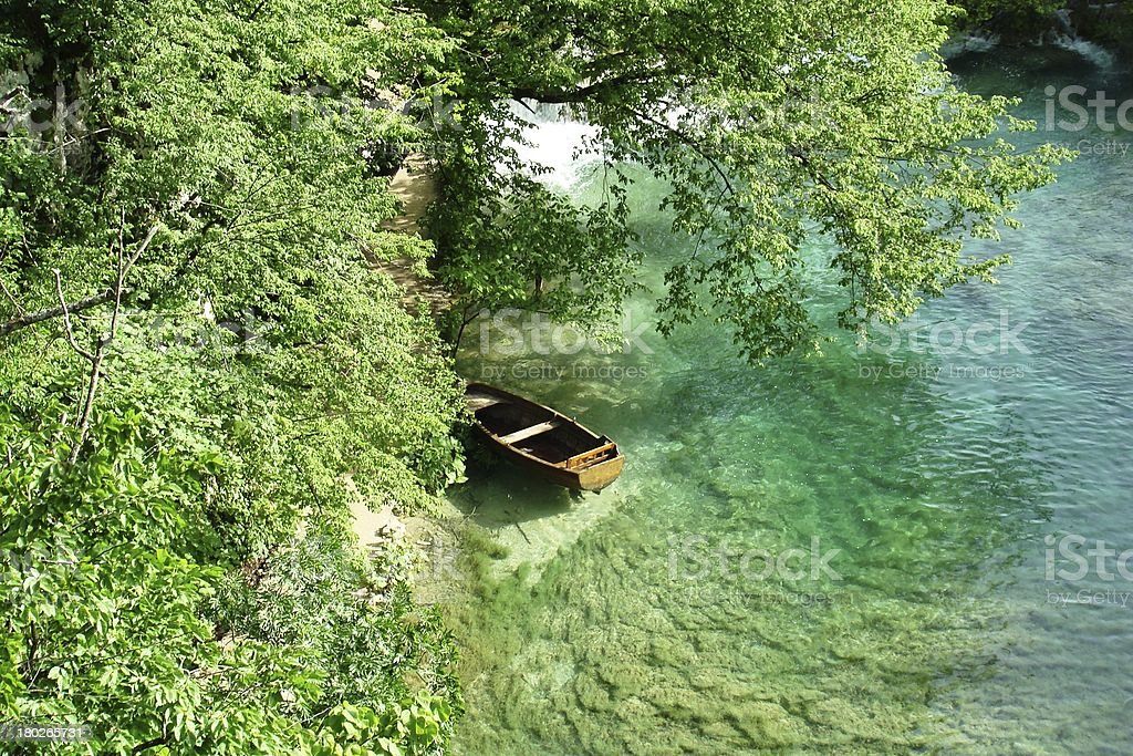 Wooden Rowboat in Lake Surrounded by Green royalty-free stock photo