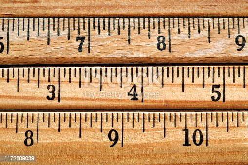 A close up of four wooden rulers stacked on top of each other.