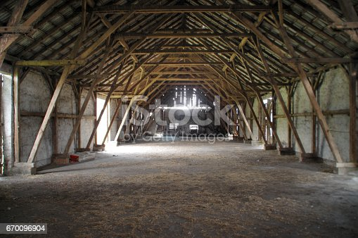 Empty rural barn with wooden supports and remains of hay on the floor