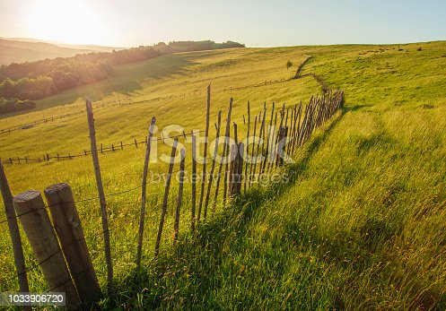 1155573645istockphoto Wooden rural fence of mountain pasture at dawn 1033906720