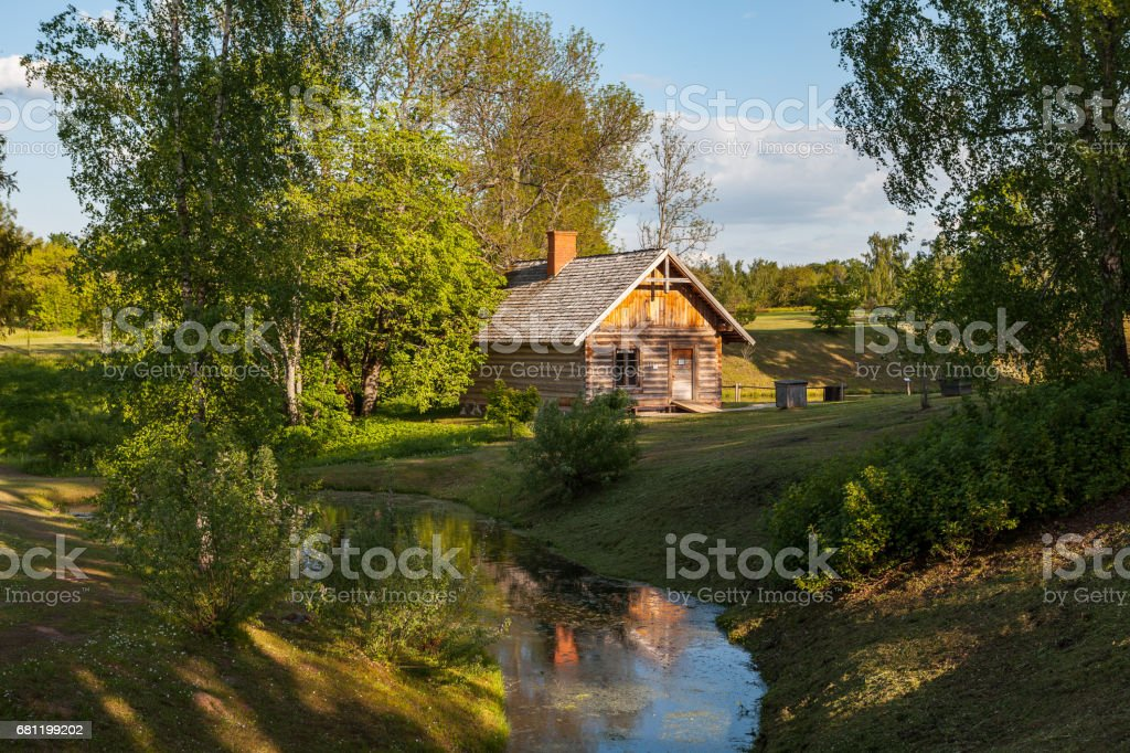 Wooden rural house and pond. Latvian countyside stock photo