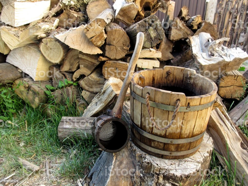 A wooden rural vintage bucket and a ladle on the background of a pile of firewood stock photo