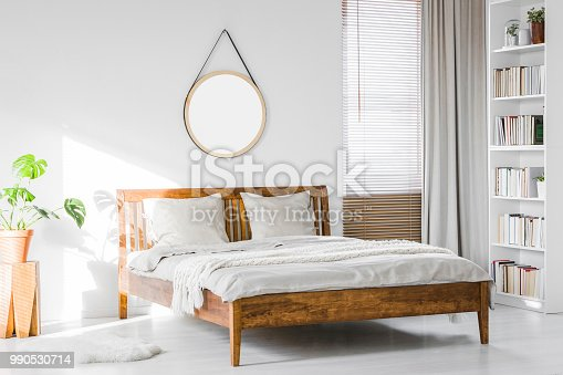 istock A wooden rustic bed frame and a home library bookcase in a natural, sunlit hotel room interior with white walls 990530714