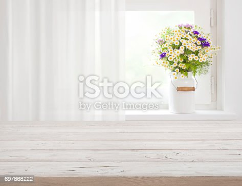 697868238 istock photo Wooden rustic table in front of wild flowers on windowsill 697868222