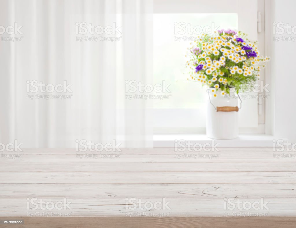 Wooden rustic table in front of wild flowers on windowsill stock photo