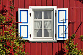 Wooden rustic painted window in small cottage house
