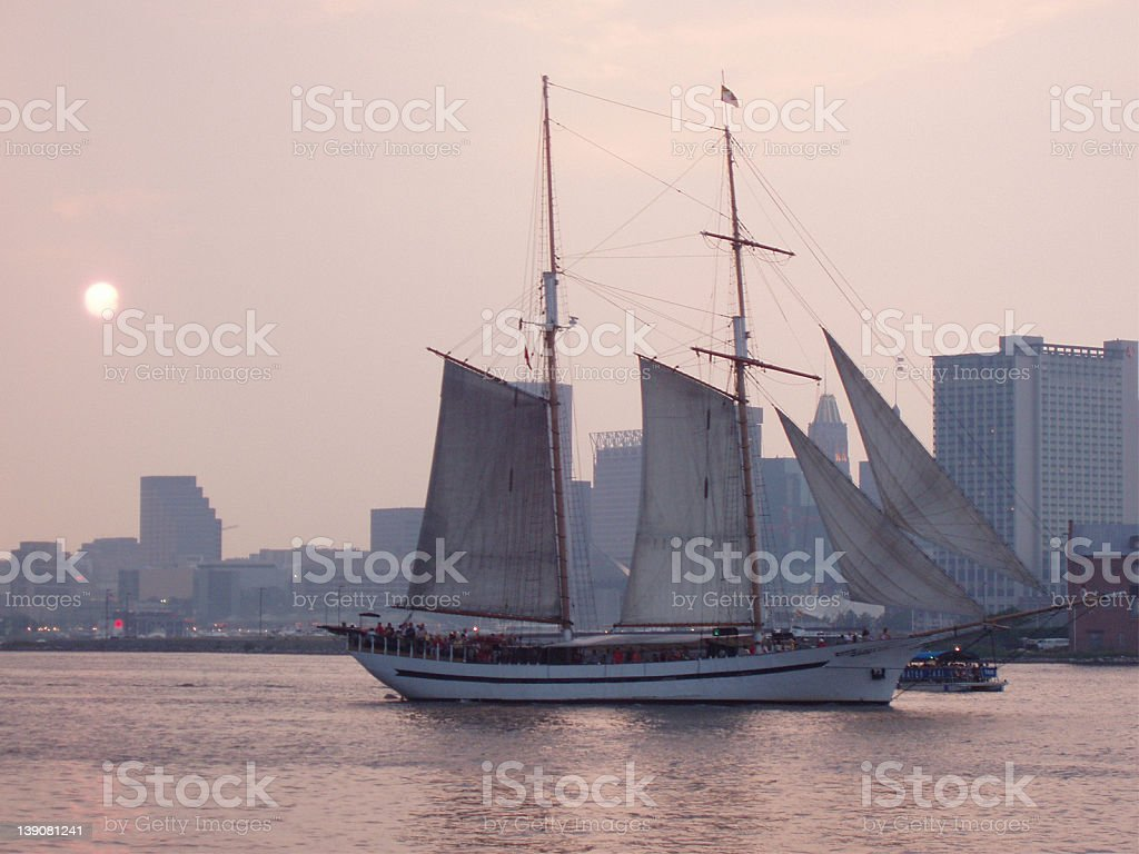 Wooden sail boat in a harbor at sunset royalty-free stock photo