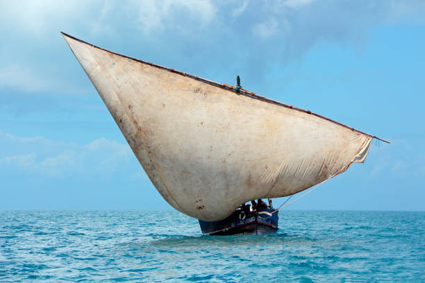 Wooden sailboat (dhow) on the open sea with clouds, Zanzibar stock photo