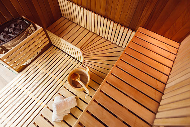 Wooden sauna room Interior of a wooden sauna room,with towels,bucket and ladle, view from the top sauna stock pictures, royalty-free photos & images