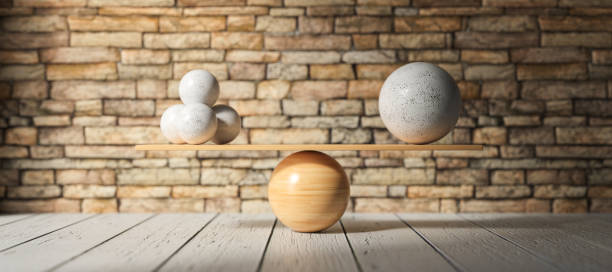 wooden scale balancing one big ball and four small ones - 3D rendered illustration stock photo