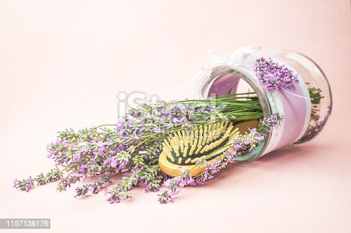 1169941952istockphoto Wooden scalp and massage brush and hair comb with lavender flowers on pastel pink background. 1157136176