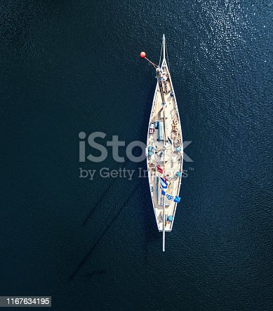 Aerial view of a wooden schooner moored in a cove.