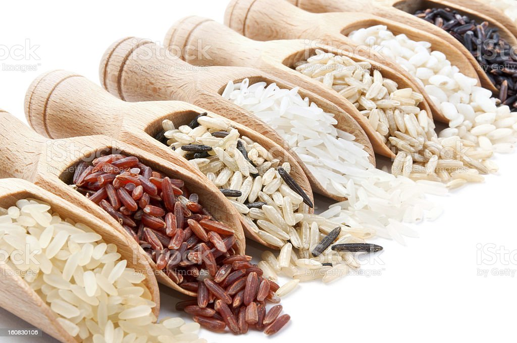 Wooden scoops with different rice types scattered from them stock photo