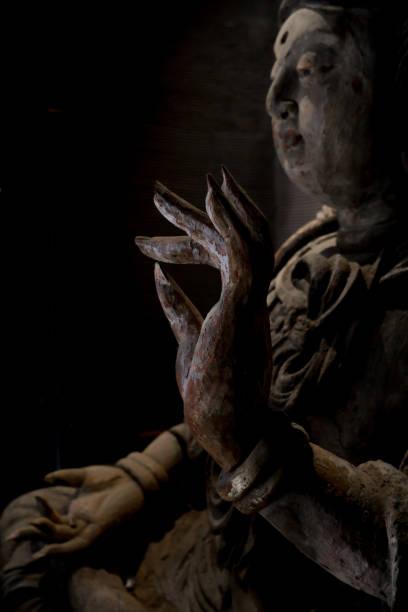 houten sculptuur van guanyin buddha - foto's van hands stockfoto's en -beelden