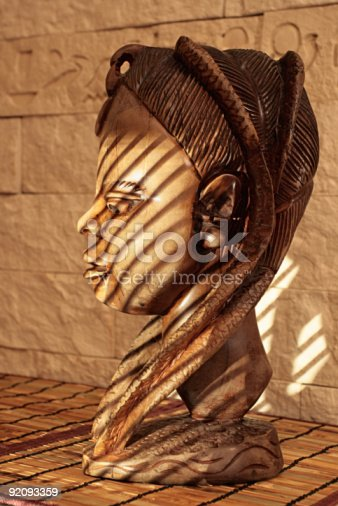 Ancient wooden sculpture from Africa on a sunlight. A head of the woman.