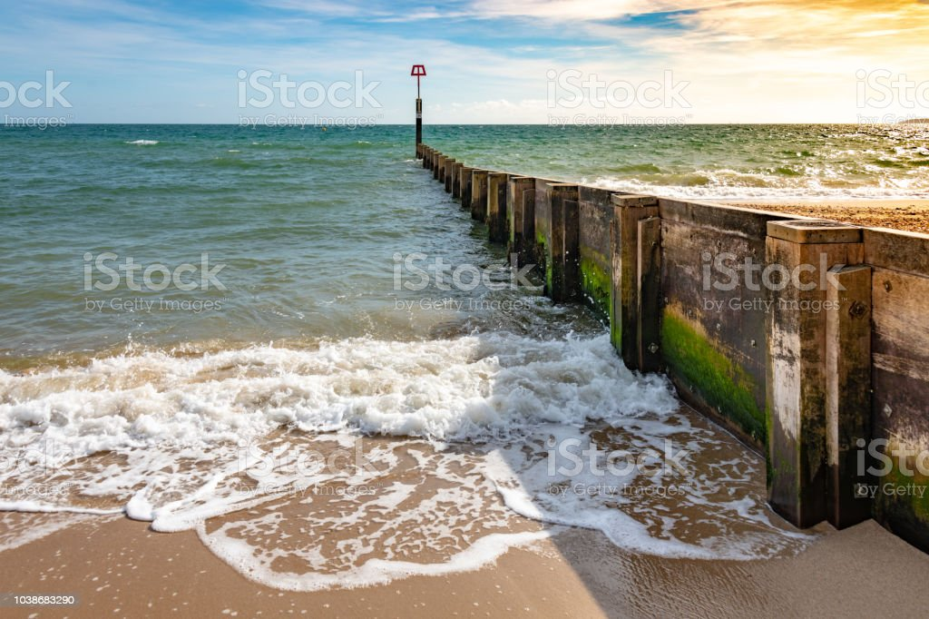 Wooden sea defense groyne on the beach stock photo