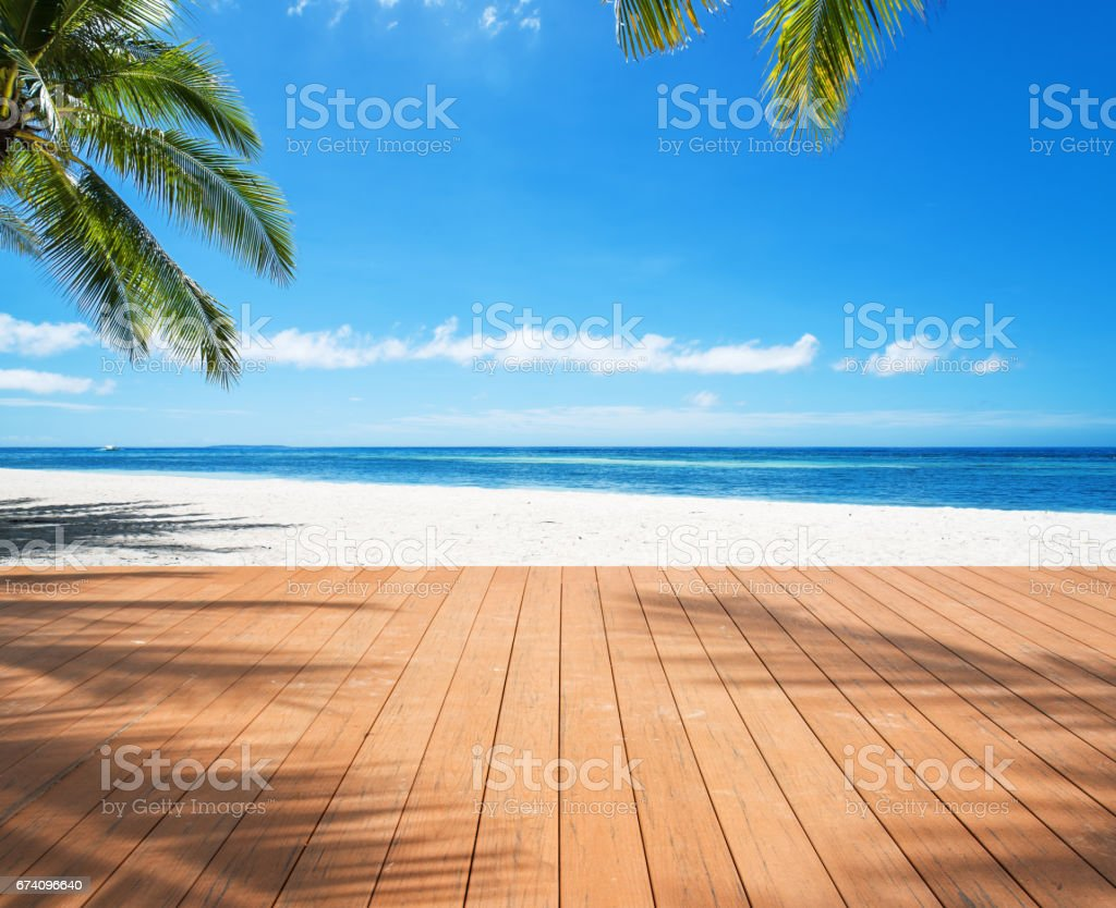 Wooden sea view terrace under palm trees beside tropical beach stock photo