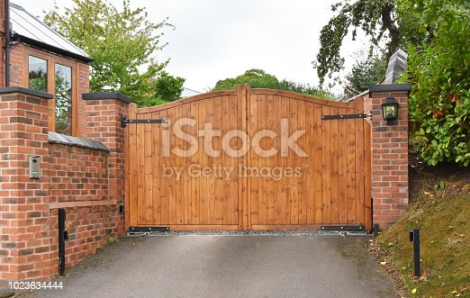 A wooden security gate on the driveway of a residential house with keypad operated lock