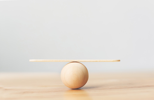 Wooden seesaw scale empty balancing on wooden sphere on wood table
