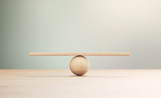 Wooden seesaw scale sitting on wood surface in front of defocused background. Balance concept.