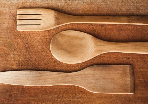 wooden serving spoons and fork on wooden surface - paletten kopfbrett stock-fotos und bilder
