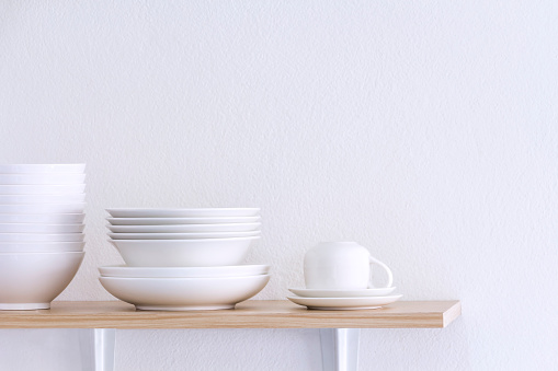 Wooden shelf template isolated on white wall background which on set stacked white bowls and plates as items tableware for decorated interior or montage of your product on shelf with copy space.