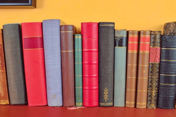 Wooden shelf with historic,decorated, vintage books. Old books on yellow and claret background stock photo