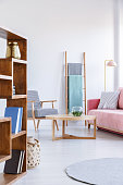 Wooden shelves and table in bright living room interior with armchair and pink settee. Real photo
