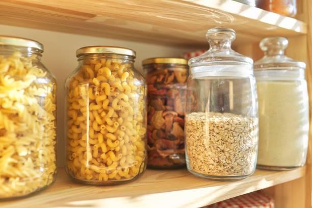 Estantes de madera en despensa para almacenamiento de alimentos, productos de grano en frascos de almacenamiento - foto de stock