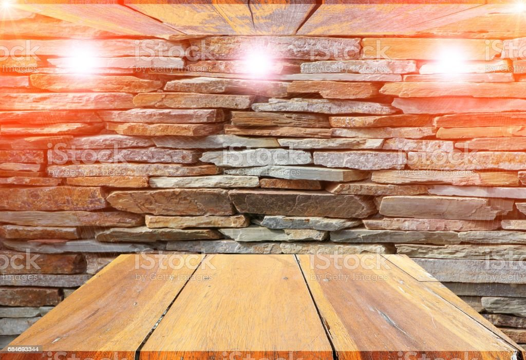 wooden shelves top empty and floor ceiling in stone wall background with reflect light for product display stock photo