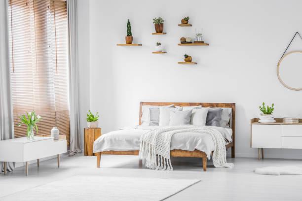 holzregale mit pflanzen über ein bequemes doppelbett in einem geräumigen apartment zimmer interieur mit weißen möbeln und wänden - sideboard skandinavisch stock-fotos und bilder