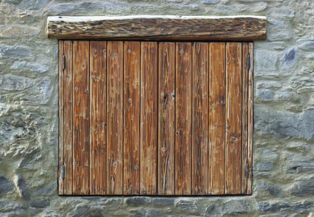 persianas de madera cerradas sobre una fachada de piedra - foto de stock