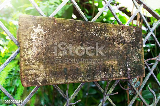 924754302 istock photo wooden sign board hanging on steel fence 1059052984