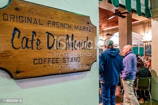 New Orleans, USA - Dec 11, 2017: Wooden sign denotes the entrance to the historic Cafe Du Monde restaurant along Decatur Street. Night scene where two patrons walked in.